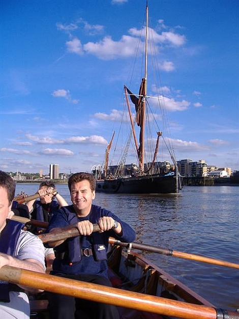Rowing a Montague whaler on the London River, with a Thames barge in the background