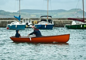 Jim's Justin Adkin rowing skiff off to sea.  Photograph by Laurence Madill