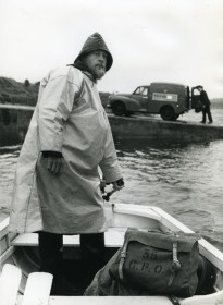Postman using boat to deliver mail at Badluarach in Inverness