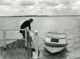 Postman using boat to deliver the mail at Poole, Dorset