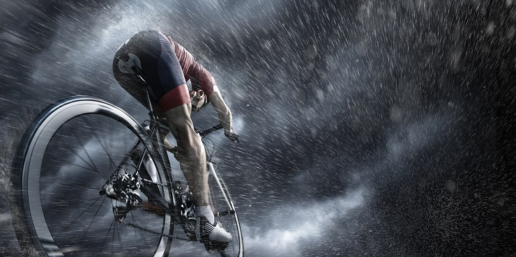 Professional cyclist under stormy sky