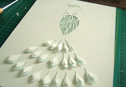 Peacock papercut with soft blue background paper