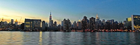 The Manhattan skyline from the East River. The cranes constructing One World Trade Center can be seen on the far left. Red, white and blue lights glow on the Empire State Building on Veterans Day 2012. The Chrysler Building is lit up on the right center of the photo.