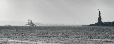 The Statue of Liberty stands as a silhoutte in the distance. This was shot from a harbor cruise ship.
