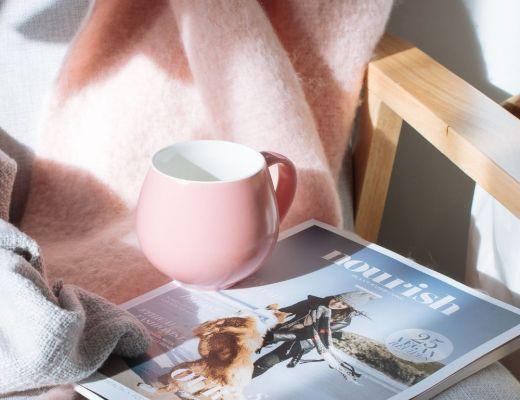 magazine with mug on top of chair