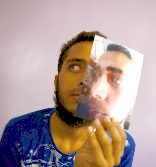 Photo of a boy holding a photo of himself in his left hand