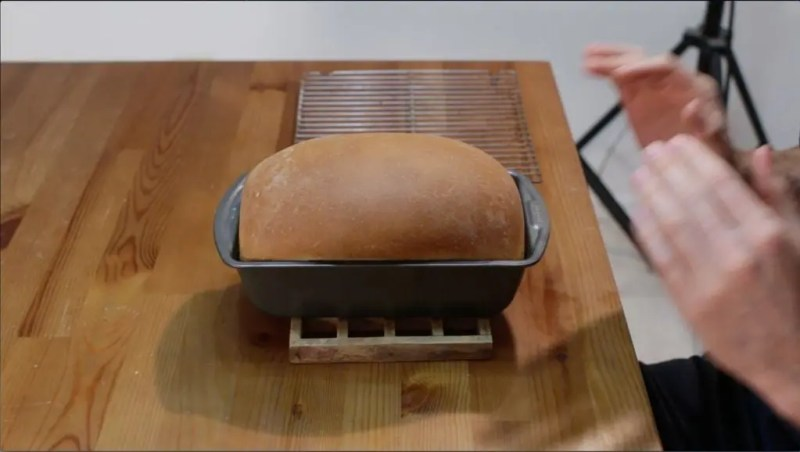 Light golden brown loaf of bread sitting in a pan on a table.