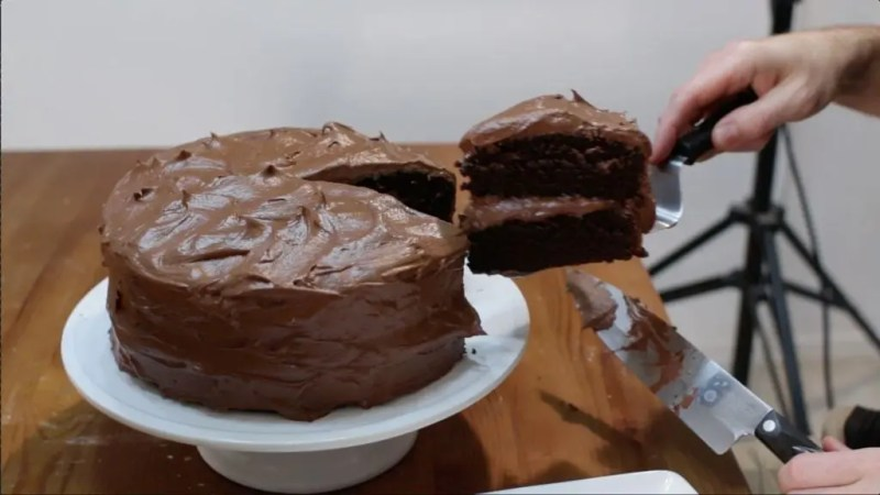 Large chocolate cake on white cake stand and man holding a slice with metal cake spatula.