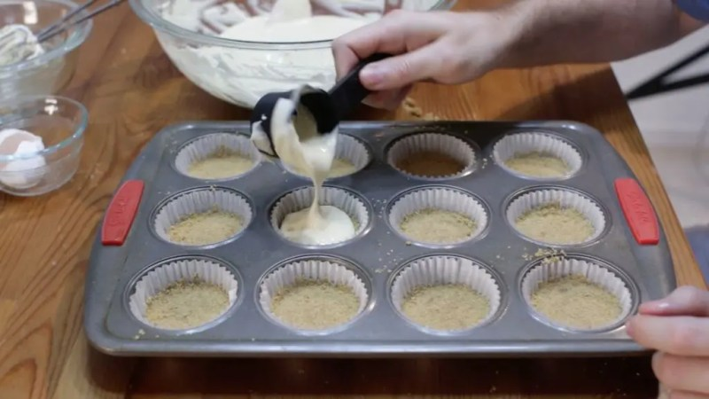 Mans hand holding a measuring spoon pouring cheesecake filling into a muffin pan with crust.