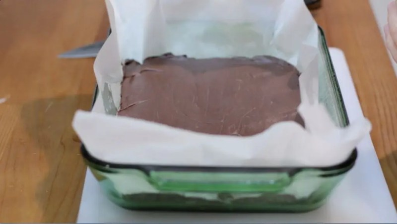chocolate fudge sitting in a parchment paper lined green glass pan on top of table.