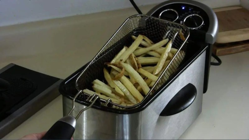 A batch of homemade french fries in a silver deep fryer on a counter.