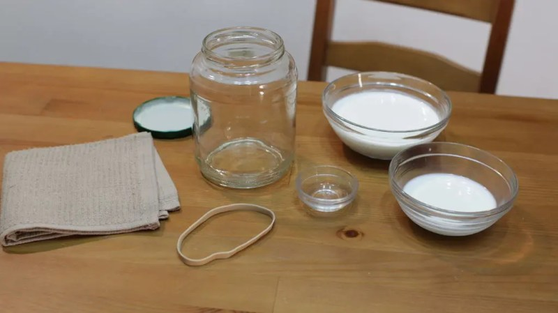 Assortment of glass bowls on a wooden table containing cream, butter, and vinegar.