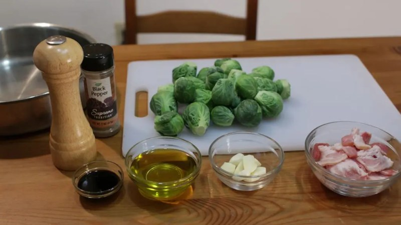 A variety of roasted Brussels sprouts ingredients in glass bowls on a wooden table.
