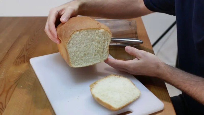 Man holding a loaf of white bread with a slice of it on a white cutting board.