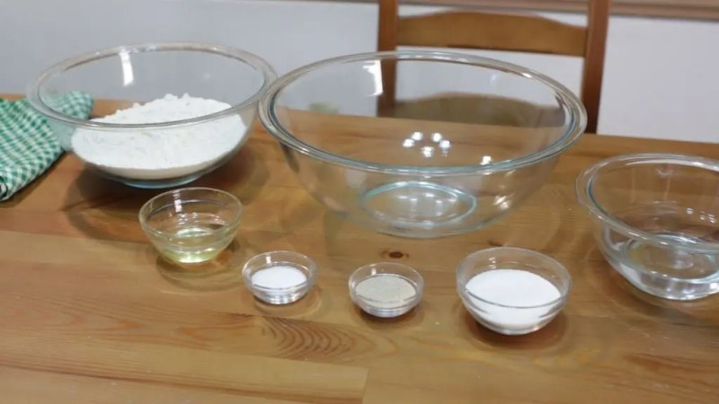 Several white bread ingredients in glass bowls sitting on a brown wooden table.