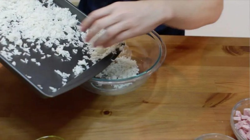 Sheet pan with cooked chilled rice being placed into a glass bowl