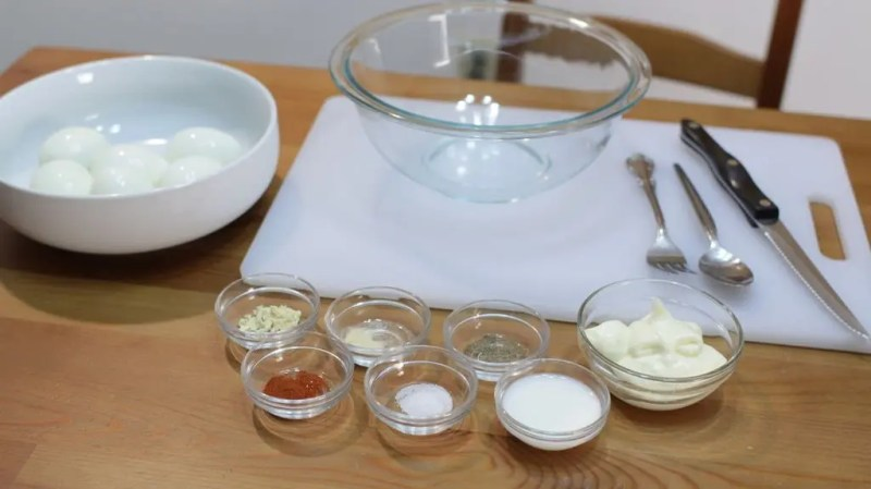 an assortment of ingredients in glass bowls to make deviled eggs.