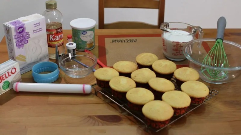 Ingredients and tools sitting on a wooden table needed for pimple popping cupcakes.