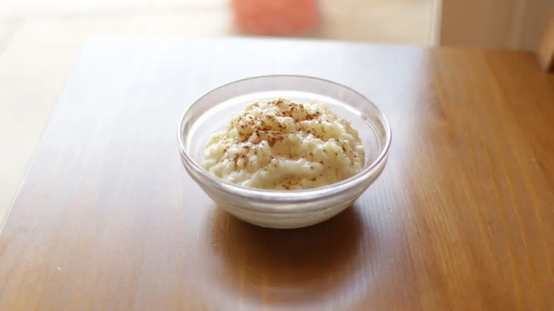 glass bowl of rice pudding with cinnamon sitting on a wooden chair