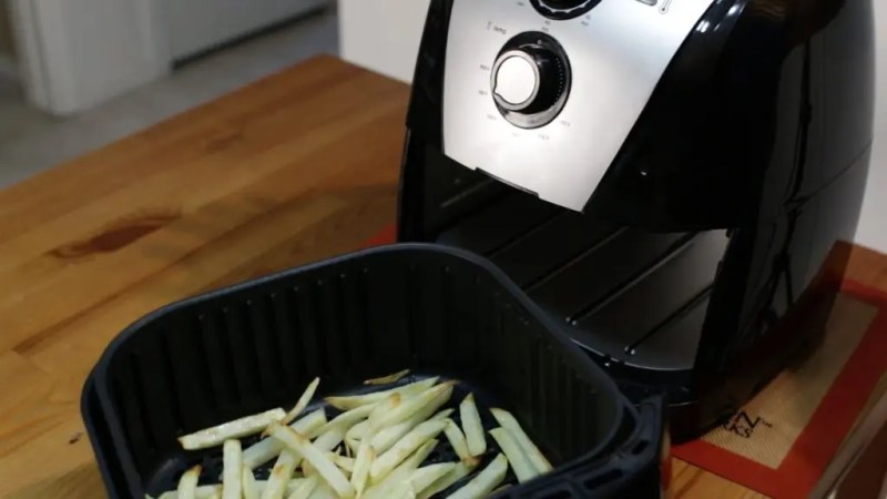 French fries in a black air fryer basket sitting on a wooden table.