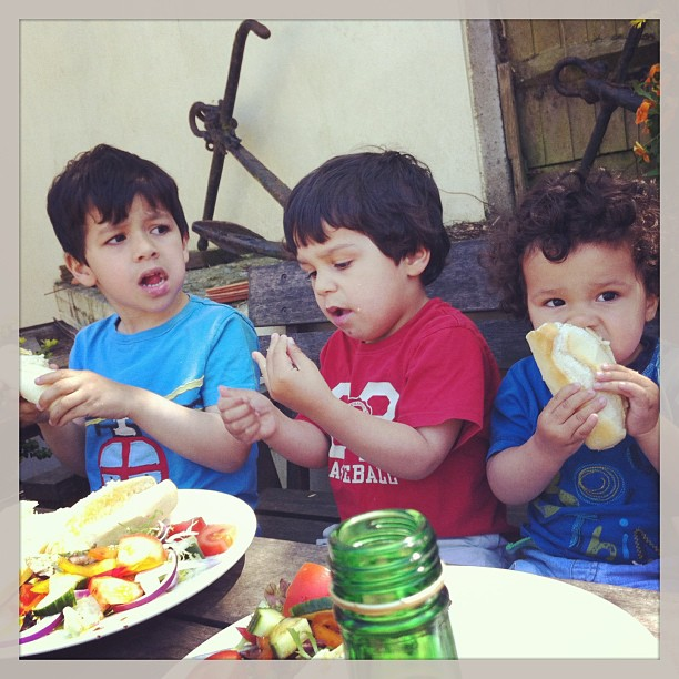 three little boys eating their lunch