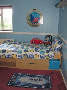 Boys room with rocket rug, numbers bedding and finding nemo wall decoration.