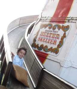 little boy coming down the helter skelter big slide in brighton, sack slide, fairground slide
