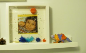 "picture of a boy in a frame signing ""yes"" signalong makaton decorated frame and toy clay dinosaur"