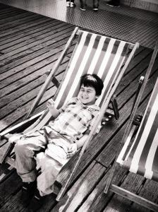black and white photograph, 4 year old boy relaxing in a deckchair on brighton pier