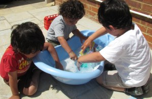 3 brothers doing water play in the garden