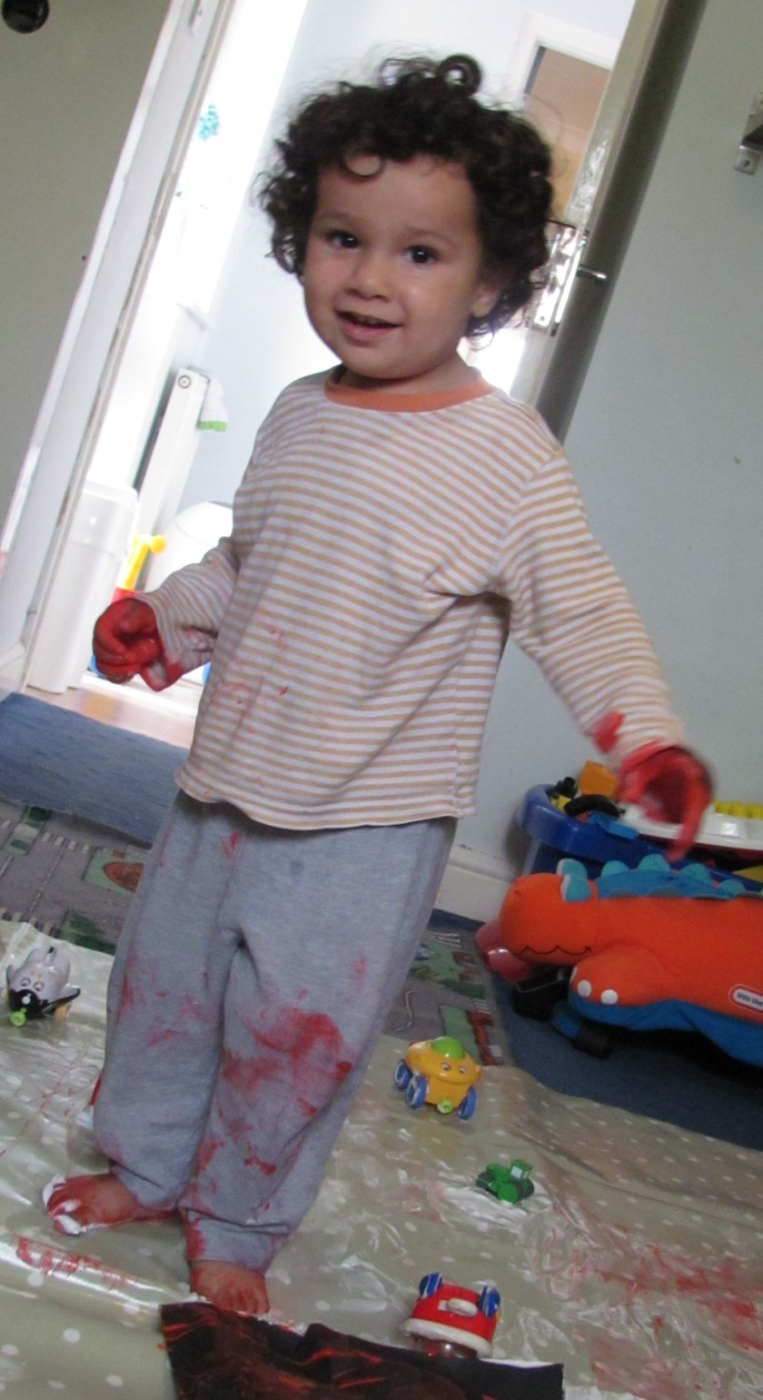 baby in painty pyjamas messy play