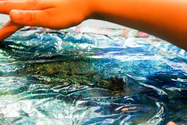 Turquoise Ocean sensory window made using a squishy gel sensory bag. It's so relaxing!