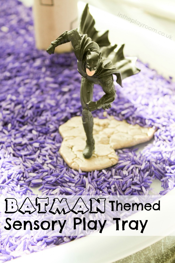 Batman sensory play tray set up with coloured rice, cardboard tube buildings and Batman superhero figures