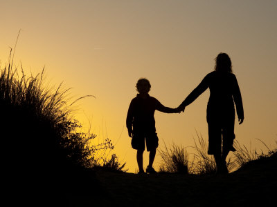 mom and child-walk-hand-in-hand-through-sand-dunes