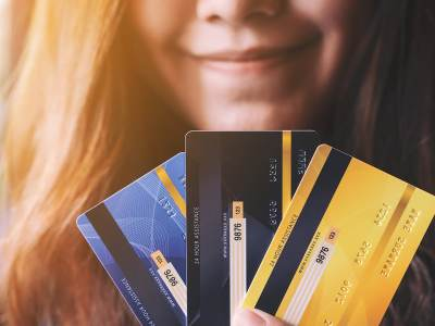 An image of a woman holding credit cards.