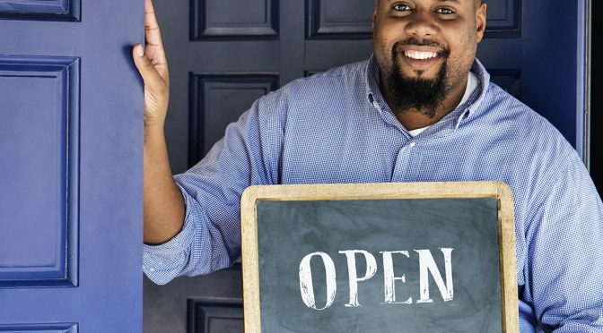 """Man standing at a blue door with a sign in his hand that reads """"Open."""""""
