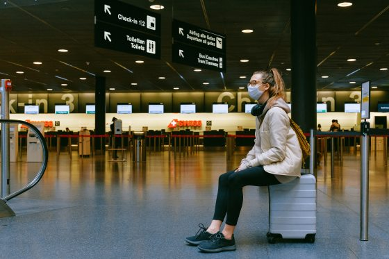 Woman sitting on luggage in an empty airport