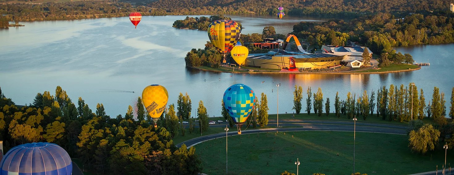 Hot air balloons over Lake Burley Griffin and the National Museum of Australia in Canberra. This is the main image on the website of the 2021 Australian Public Health Conference.