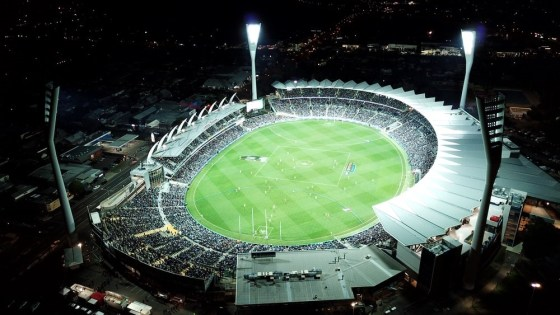 An AFL game at night in a stadium. Photo by Daniel Anthony, source Unsplash.