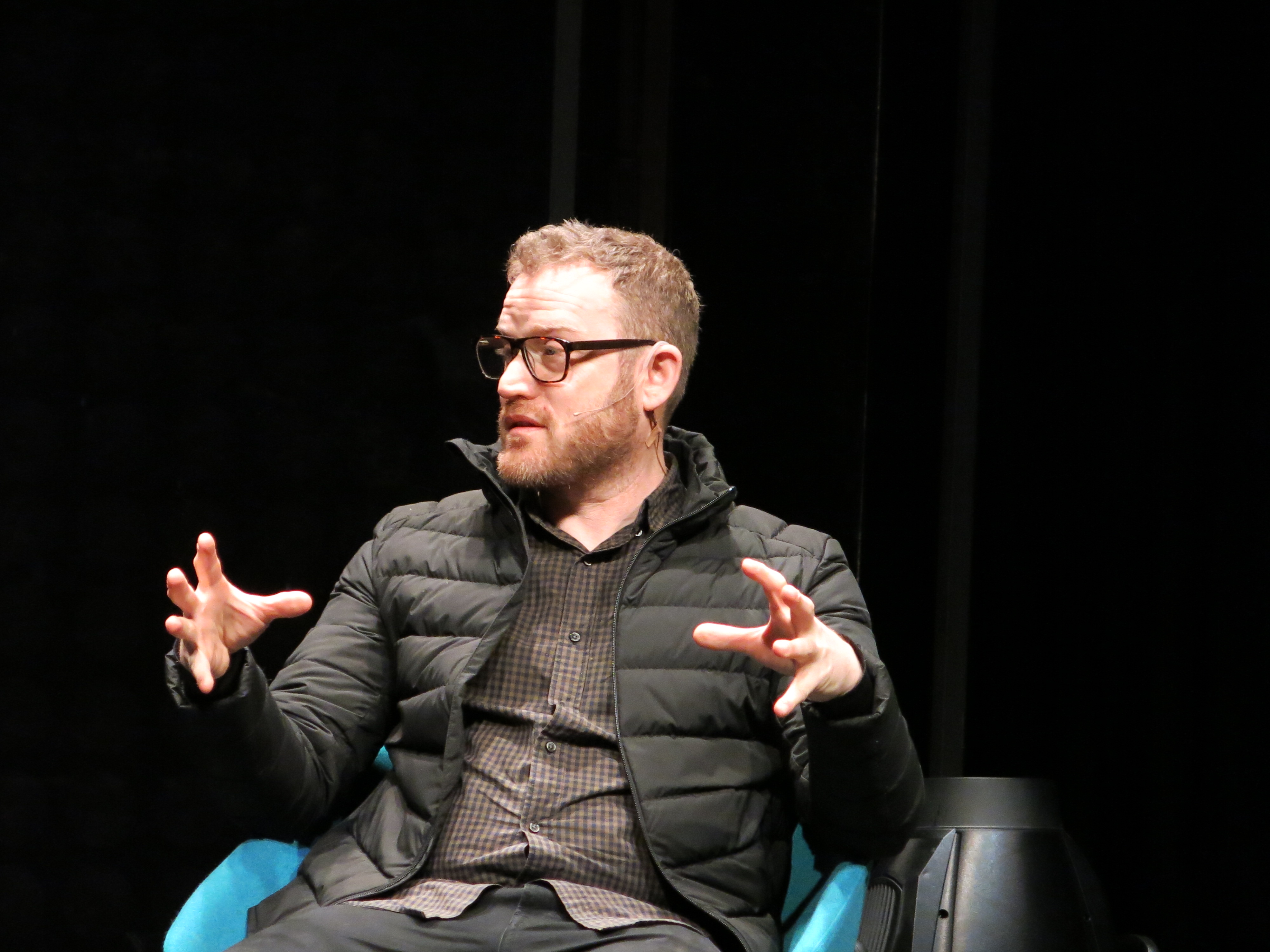 John Safran gestures with both hands while seated on a stage in Christchurch.