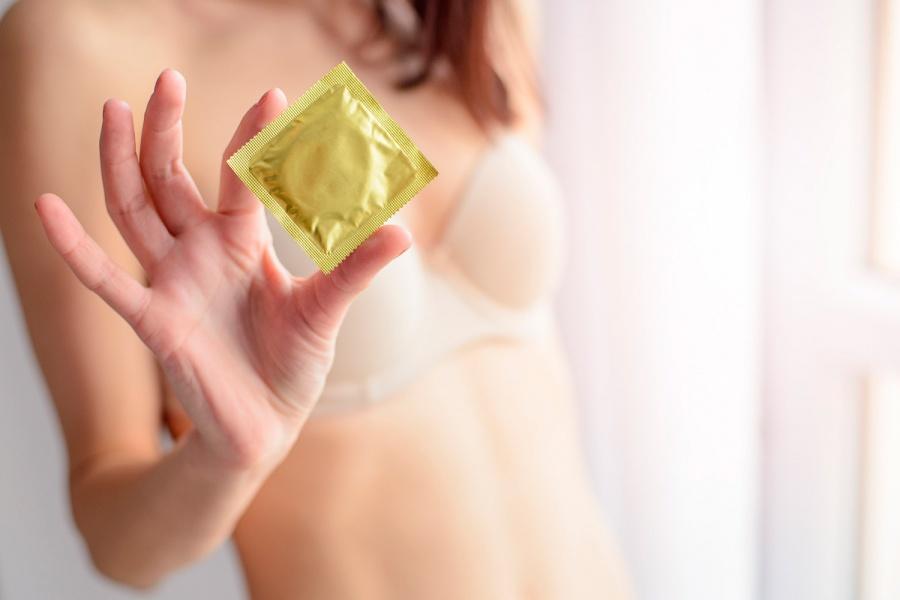 девушка держит презерватив