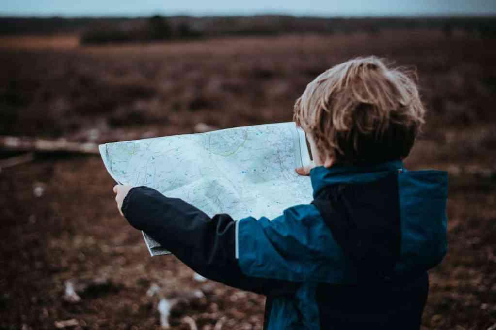 kind kijkt op een landkaart in een weide omgeving - hoe ga je om met een introvert kind