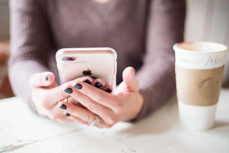 vrouwelijke handen met telefoon en koffiebeker - verschillen tussen introvert en extravert