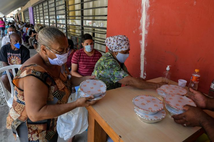 Residents receive meals at a soup kitchen in Sao Paulo.