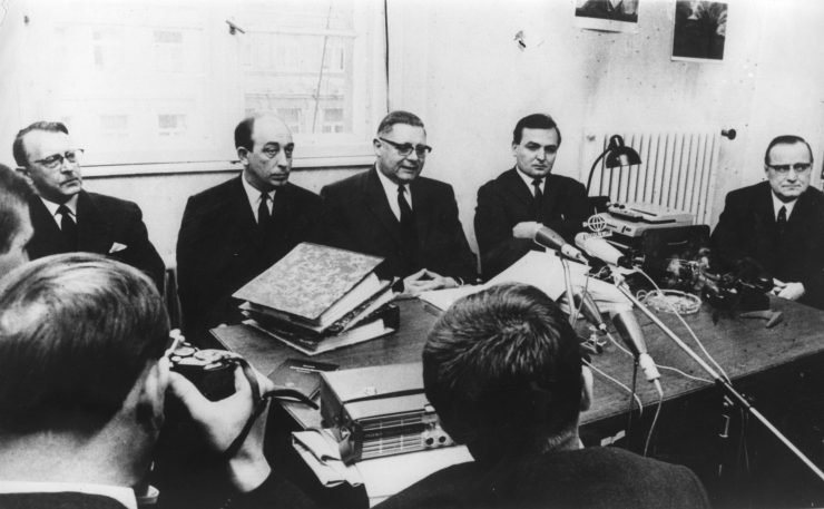 Black and white photo of men crowded around a conference table.