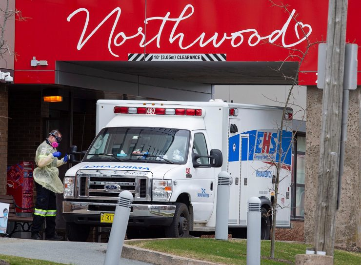 A paramedic walks around an ambulance at a nursing home.
