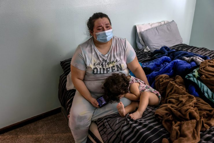 A young woman sitting on a bed with a small child who is hiding her face.