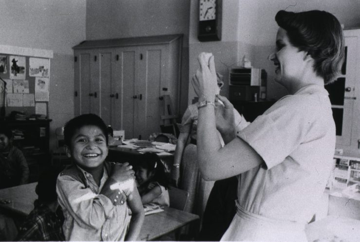 Smiling boy rolls up his sleeve to get a shot from a nurse
