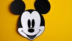 obrázok mickey mouse na žltom pozadí, ktorý predstavuje Disney (DIS)