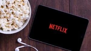 Logo Netflix (NFLX) na tablete so slúchadlami na ušiach a misou s kukuricou v okolí.